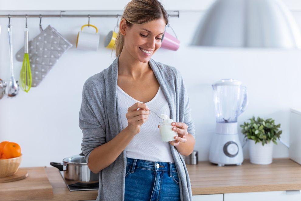 Γυναίκα τρώει γιαούρτι στην κουζίνα